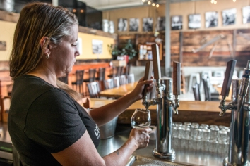 Craft Kitchen & Brewery Owner Courtney Stevens is pouring a brew in the taproom -photo courtesy of Craft Kitchen & Brewery